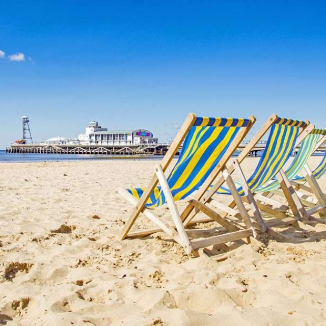 4 deckchairs lined up on the beach with Bournemouth pier in the background