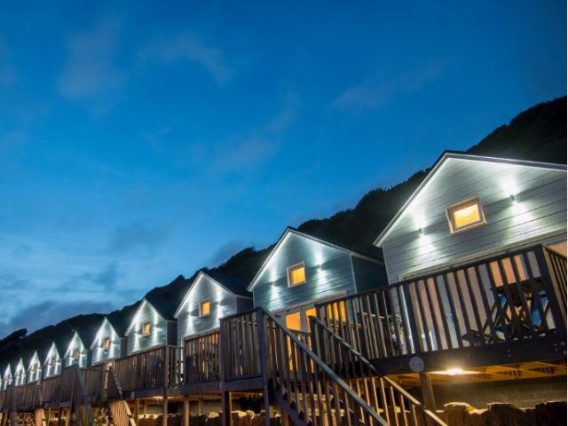 Beach huts all lit up at dusk