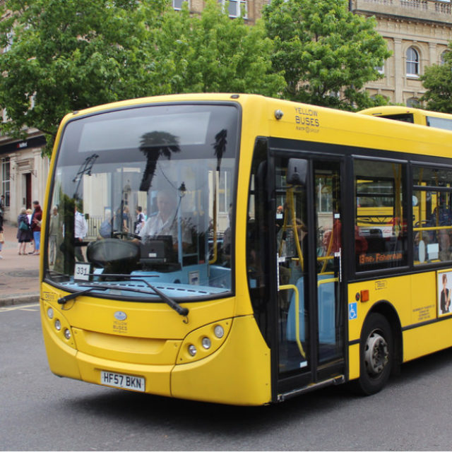 A yellow bus driving around Bournemouths town centre