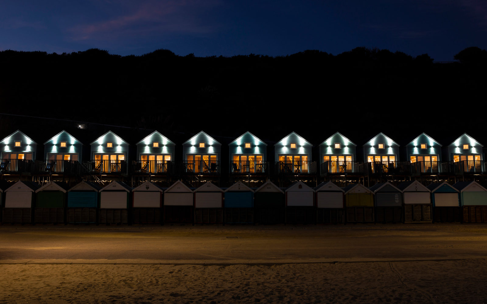 Wide shot of the bournemouth beach huts all lit up at night