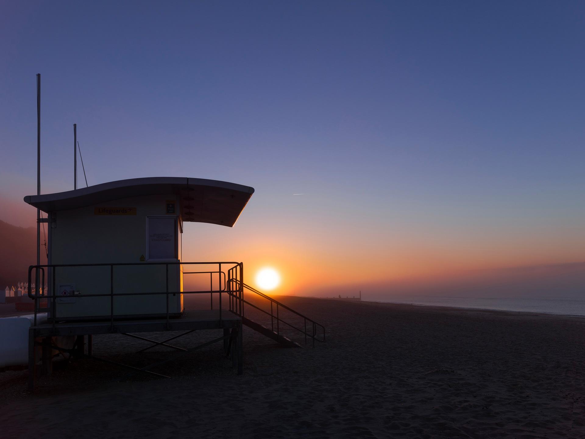 Sun slowly rising behind a lifeguard hut on boscombe beach