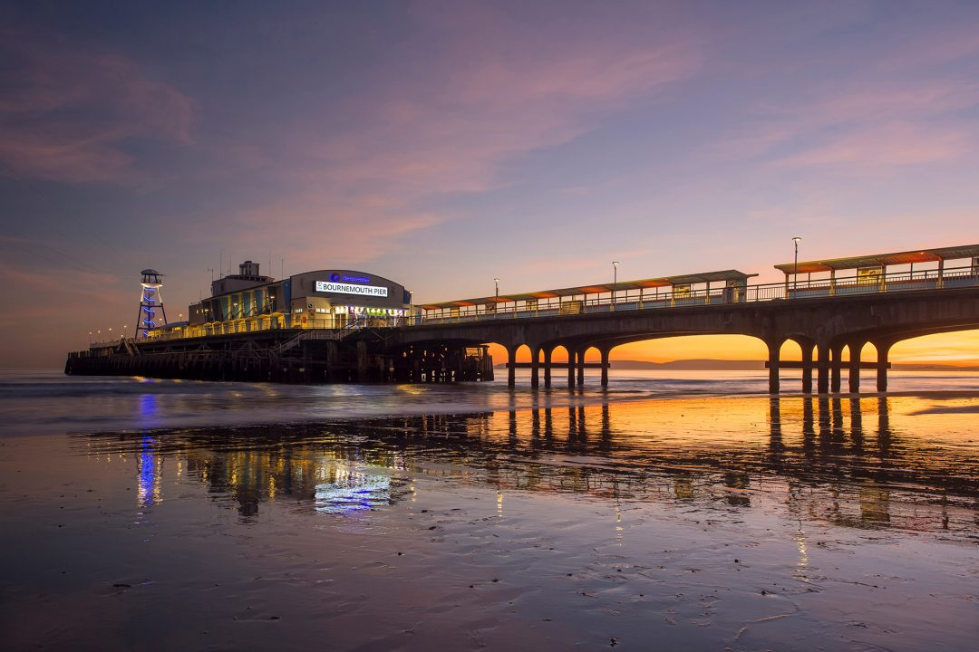 Bournemouth pier lighting up the purple and orange sky at dusk