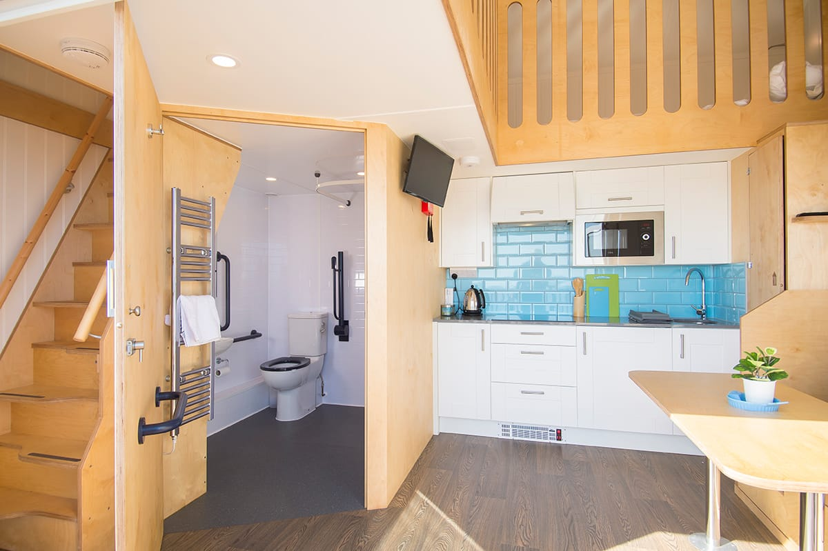 Interior shot of toilet, dining and kitchen area in the accessible beech hut