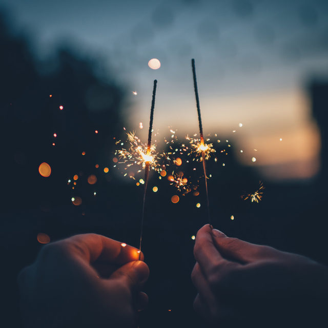 Two hands holding up sparklers at night