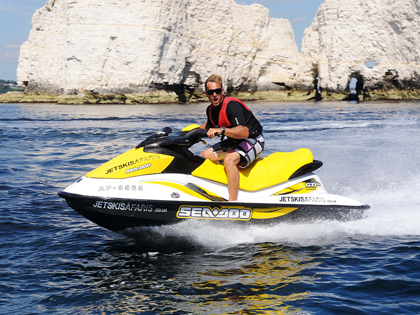 Guy poses for photo while riding his hired jet ski