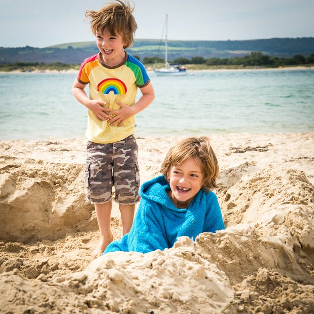 Children laughing whilst digging a hole at the beech