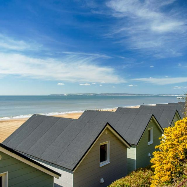 Above and behind the lodges with clear views of Dorset coastline and sky