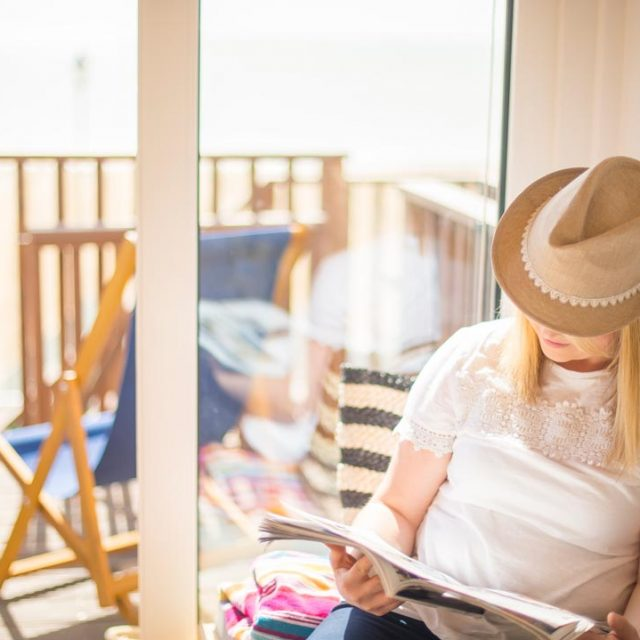Guest relaxing and reading in her beech lodge