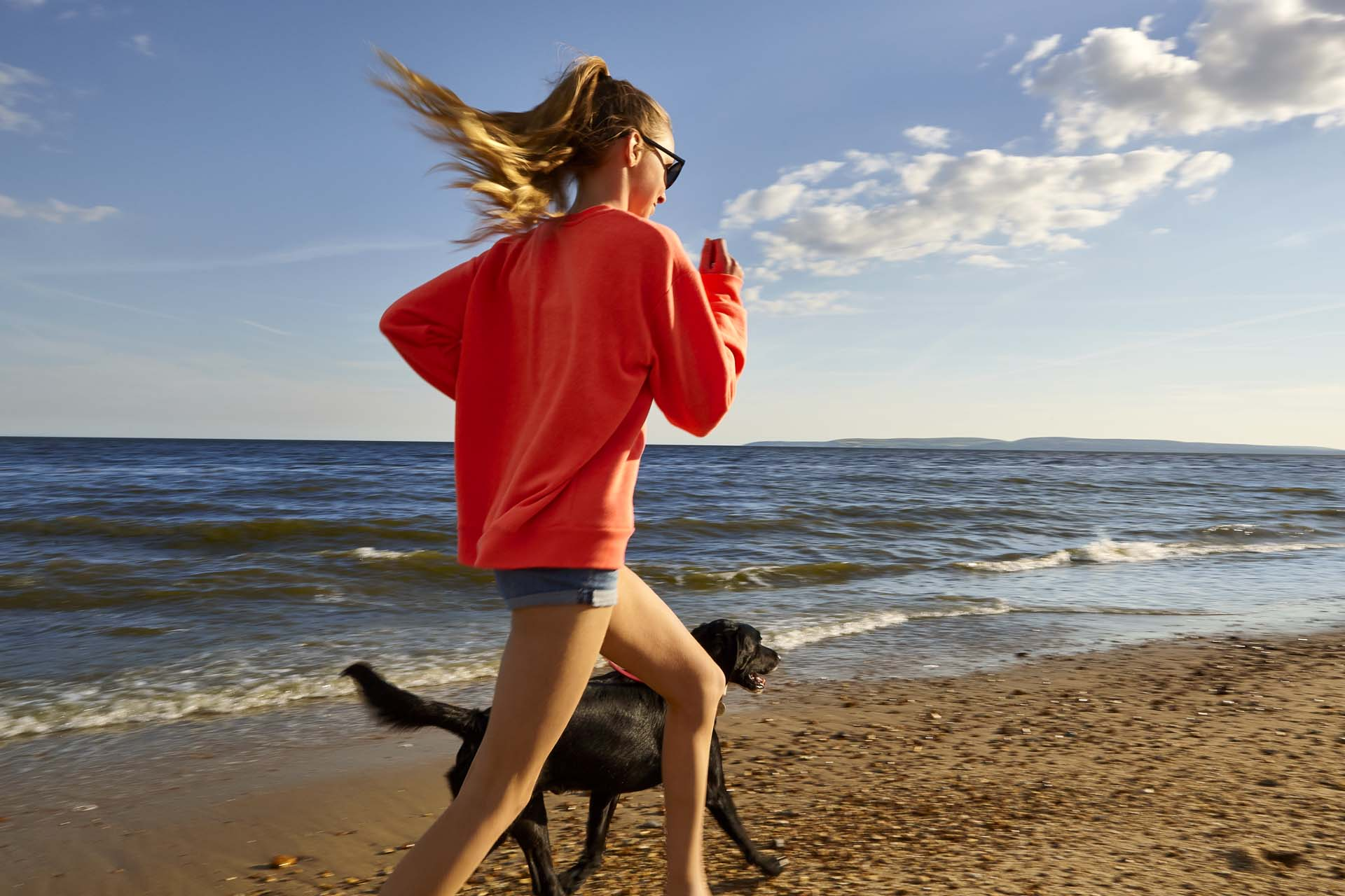 Wind in the hair beach running with teenage and lovely dog