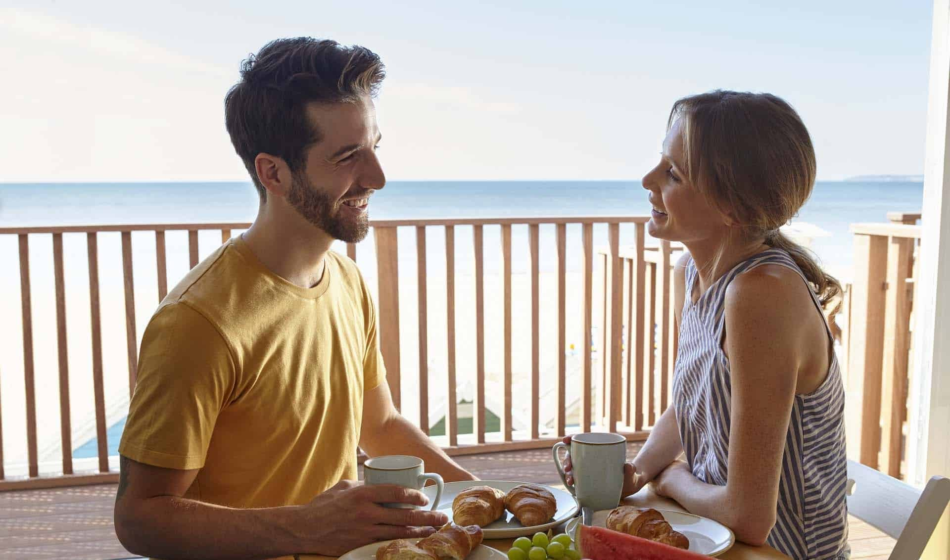couple eating breakfast with sea view from their Beach Lodge