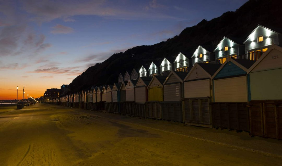 Beach lodges all lit up as the sun sets in the distance