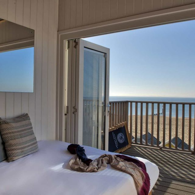 Neatly made bed with bi-fold doors wide open to see the sea