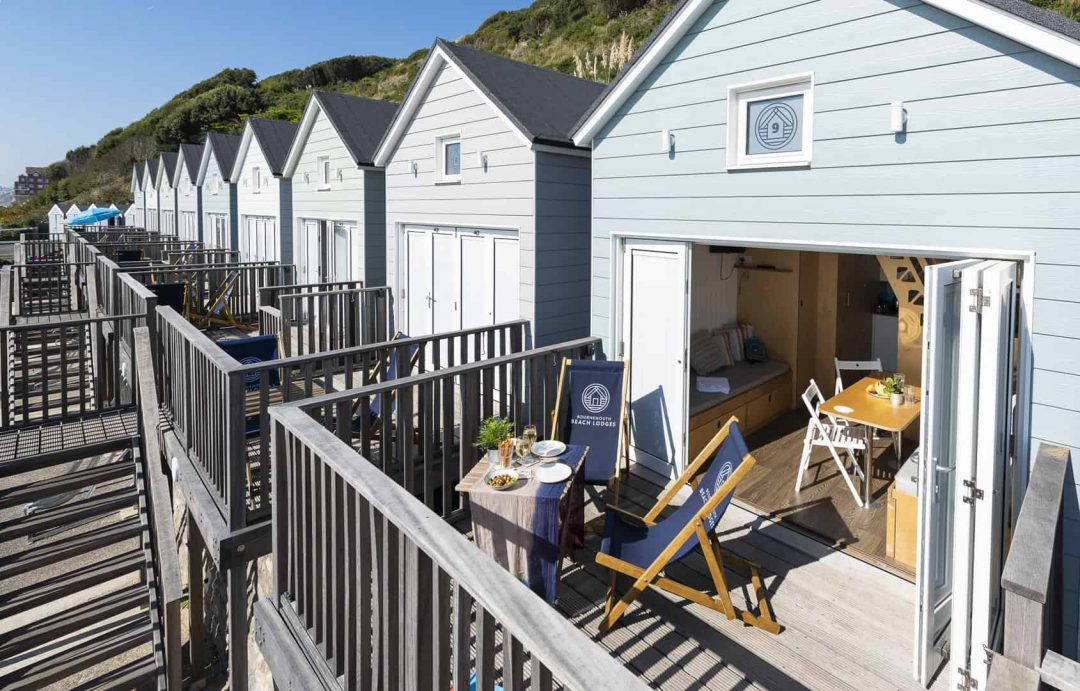 One of the Beach lodges all set up with doors open, deckchairs and table placed on decking