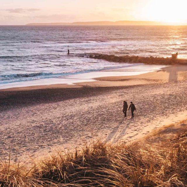 Couple enjoying a relaxing Autumn walk on the beach