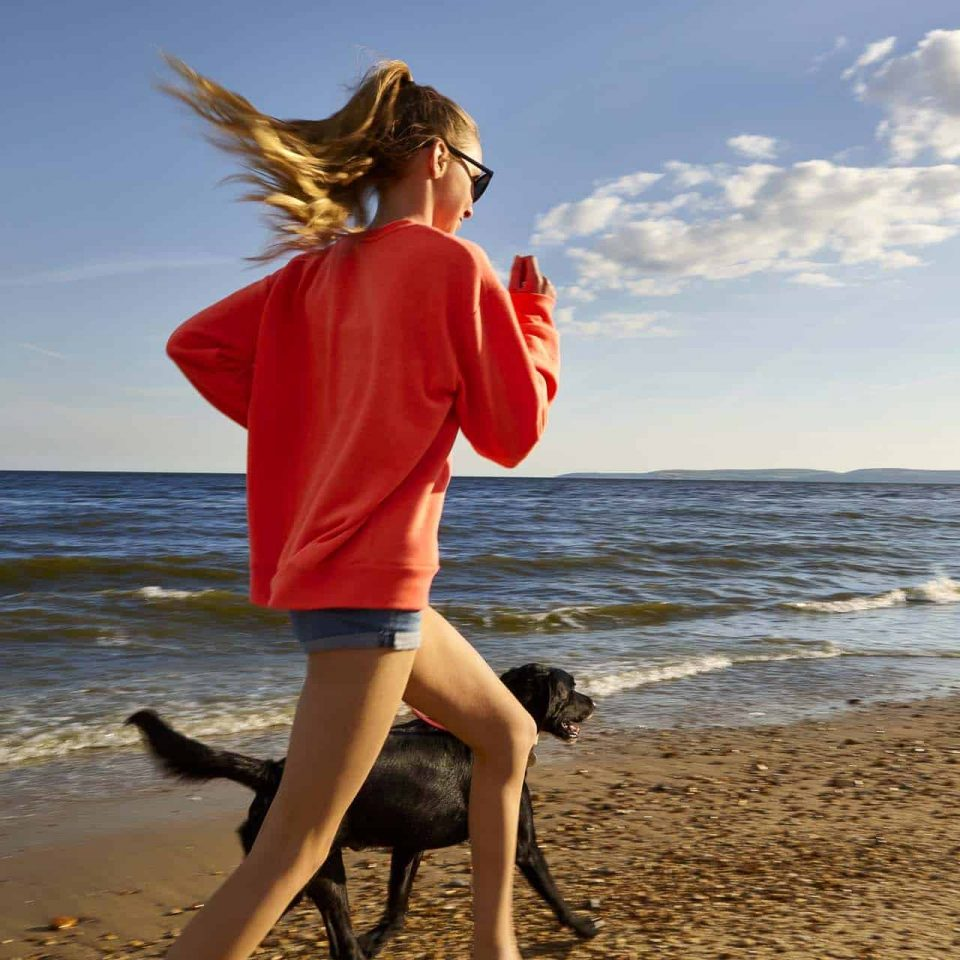 Young girl running along Bournemouth beach with her Black Labrador