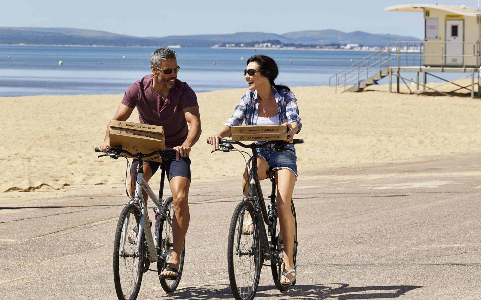 A couple cycling along the seafront with pizzas on a sunny day at the beach