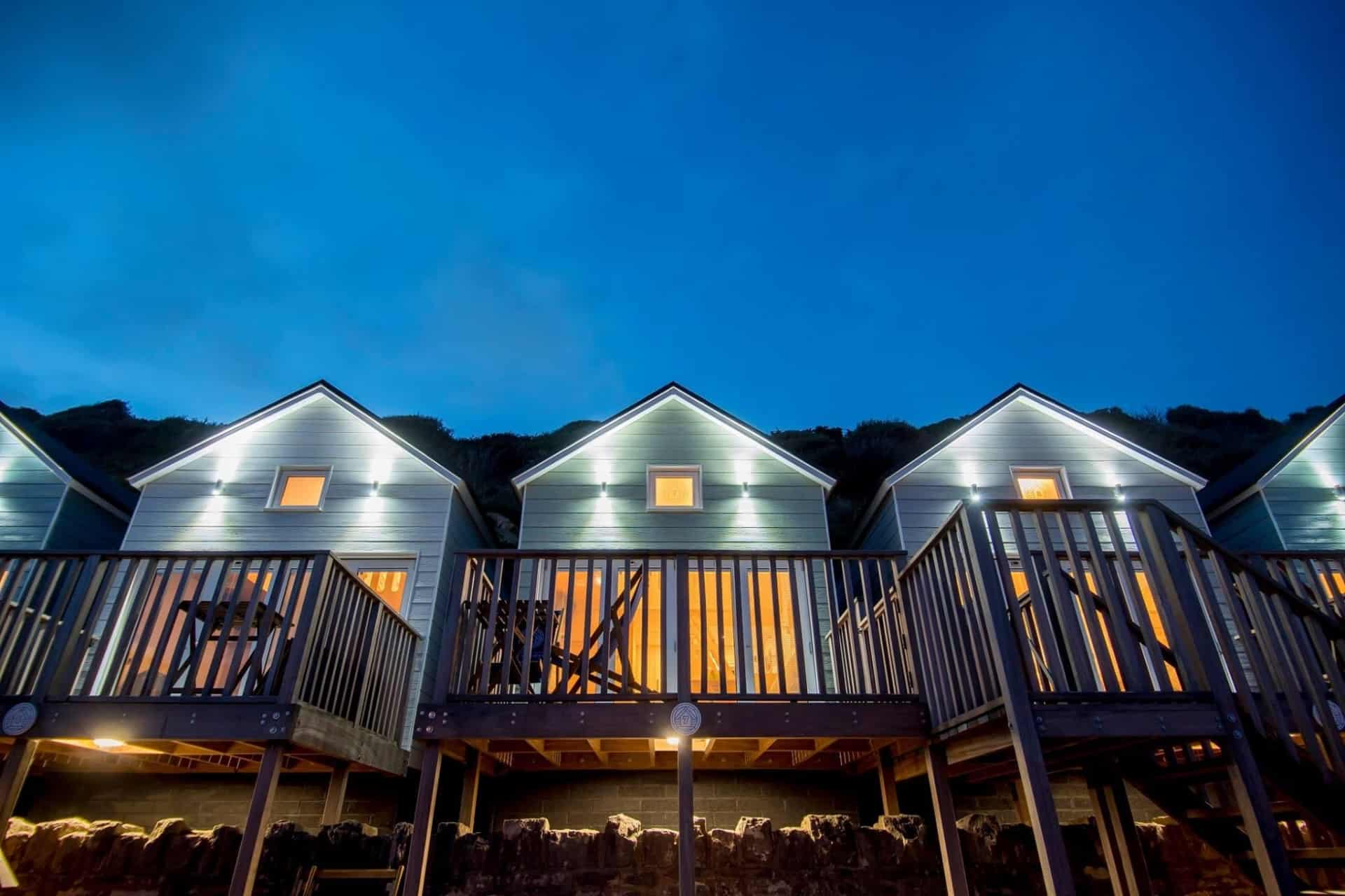 Three beach lodges lit up at night taken form the beach
