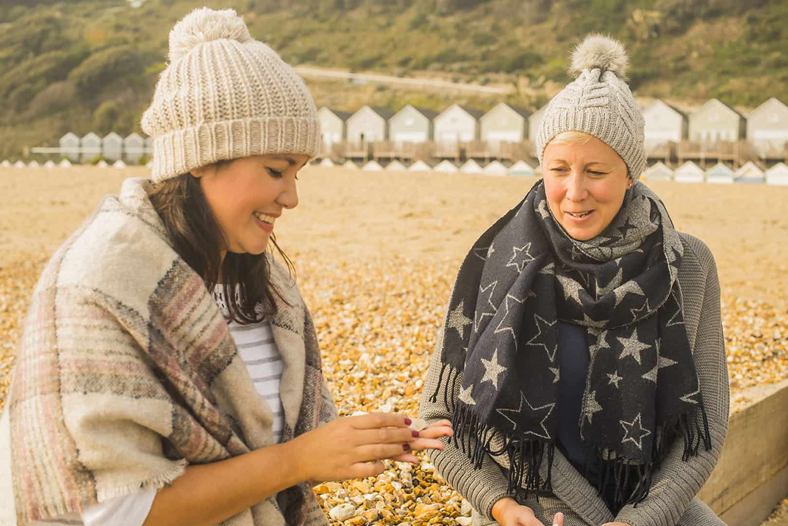 Two women sat on beach wrapped up warm with lodges in the background